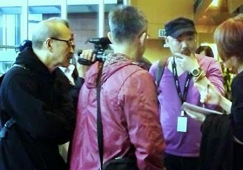 ロビーにて/取材陣に囲まれる池谷薫監督と福居正治カメラマン